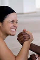 Smiling woman and young man arm wrestling, close-up