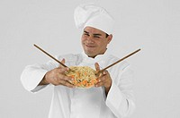 Smiling chef holding bowl of noodles and vegetables with chopsticks