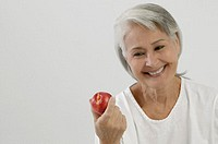 Smiling senior woman holding red apple