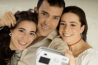 Two young women and a young man taking a photograph of themselves from a digital camera