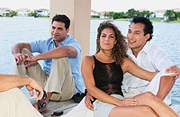 Friends sitting on dock and talking