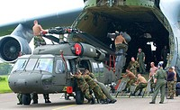 C. MONCADO AIR BASE, LA CEIBA, Honduras -- Airmen unload a UH-60L Black Hawk from a C-5 Galaxy. The C-5 is from the 137th Airlift Squadron, New York A...
