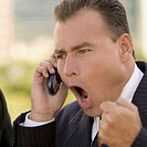 Mid adult businessman yelling on mobile phone outdoors