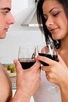Side profile of a young couple toasting with red wine
