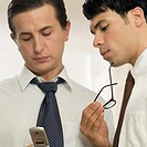 Close-up of a businessman using a mobile phone with another businessman standing beside him