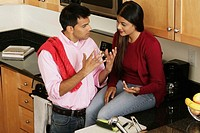 High angle view of a young man talking to a young woman in the kitchen