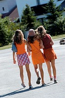 Rear view of three teenage girls walking together
