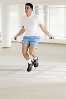 Young man jumping rope indoors