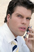 Businessman talking on cell phone, close-up