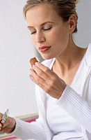 Woman eating pretzel, eyes closed