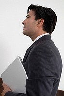 Profile of businessman holding laptop computer