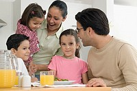 Family having lunch or dinner together in kitchen, close-up