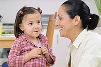 Woman with young girl who is buttoning shirt, close-up