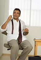 Man sitting on chair with tie undone
