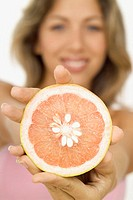 Smiling young woman holding out half of a grapefruit, close-up, selective focus, focus on grapefruit