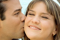 Close-up of a mid adult man kissing a young woman