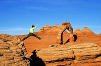 Female hiker leaping from rock to rock with Delicate Arch in background, Arches National Park near Moab, Utah, USA