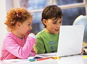 Boy and girl (6-9) using laptop