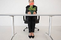 Businesswoman hiding behind plant