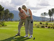 Man giving woman a golf lesson