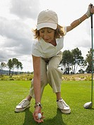 Woman placing golf ball on tee