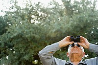 Senior man looking through binoculars