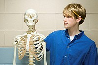 Male student stood with a human skeleton