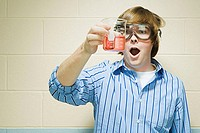 Male student holding flask of chemicals