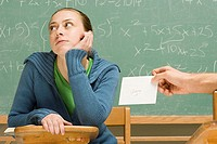 Boy passing girl a letter in class