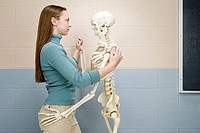 Female student dancing with human skeleton
