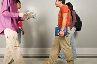 Four students walking along corridor