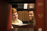 Two students reading in the library (thumbnail)