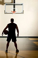 Basketball player alone in basketball court
