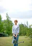 Girl standing in yard with watering can