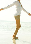 Woman standing on beach with arms out, neck down