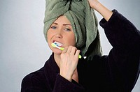 Young woman, age 20-25, brushing her teeth, holding green towel on her head, wearing black bath robe.  Left side of photo includes space for possible ...