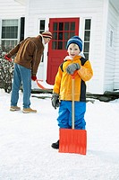Boy standing with snow shovel