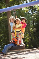 Four children swinging on tire swing