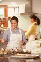 Woman decorating baked goods in bakery