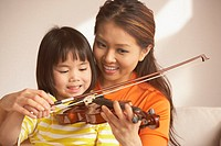 Mother helping her daughter play the violin
