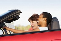 Two friends in convertible looking at map and laughing