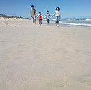 Family walking and holding hands on the beach