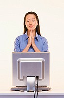 Businesswoman praying in front of computer