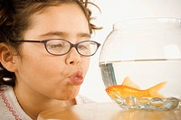 Young girl making a kissy face for a goldfish