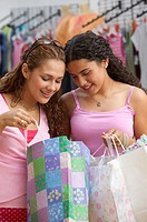 Two teenage girls looking in gift bag while shopping