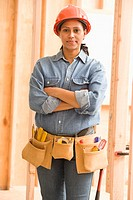 Portrait of female construction worker wearing tool belt and hard hat