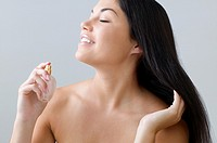 Young woman spraying perfume on herself