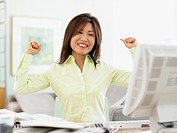 Businesswoman celebrating at her desk