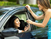Mother handing teenage daughter car keys