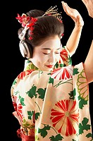 Asian woman in ethnic clothes listening to headphones